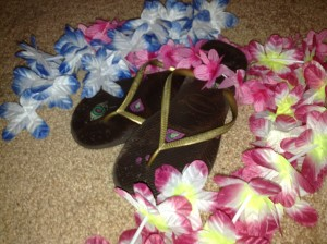 A pair of flip-flop sandals surrounded by leis