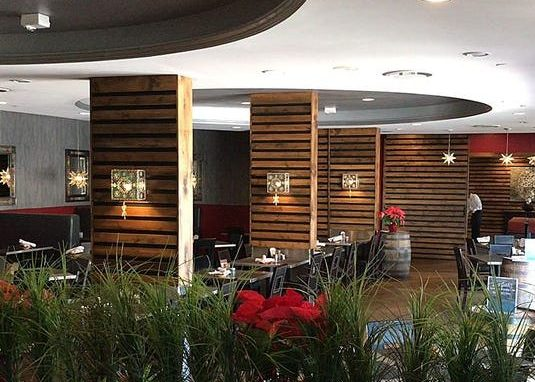 La Cosecha, with tables and booths, cut-steel decorative lamps on wooden-paneled walls, and decorative plants.